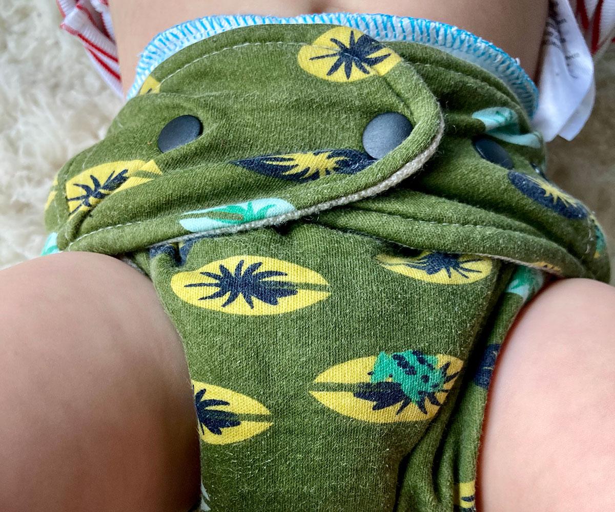 Eine grüne Stoffwindel an einem Baby